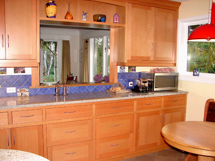 upper and lower wood cabinets and window to dining room